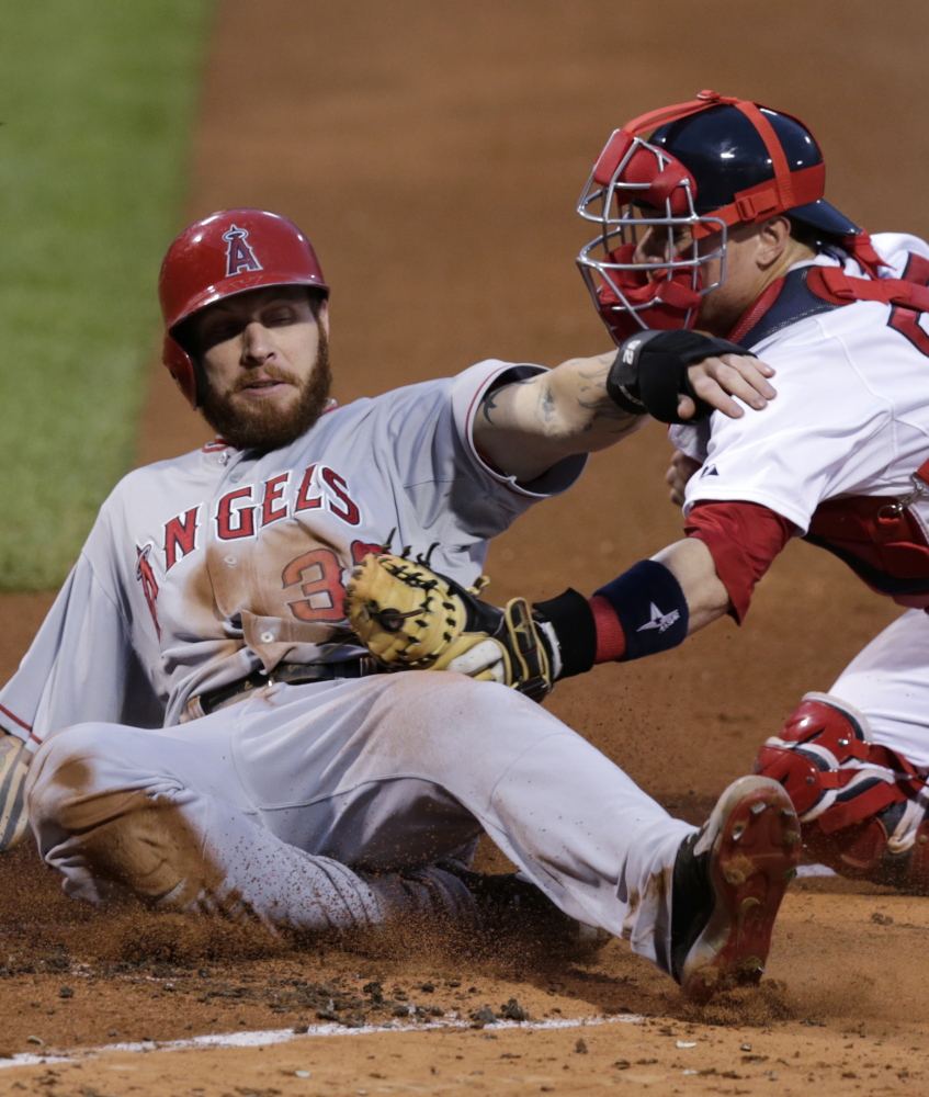 Josh Hamilton of the Los Angeles Angels is tagged out by catcher Christian Vazquez of the Boston Red Sox while trying to score on a single by Howie Kendrick during the first inning of the Angels' 2-0 victory Thursday night at Fenway Park. The Angels swept the four-game series.