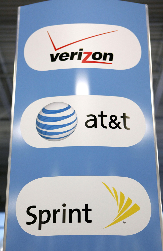 A sign for Verizon, AT&T and Sprint mobile phones is on display at a Best Buy store. Carriers are trying to lure customers with new offerings.