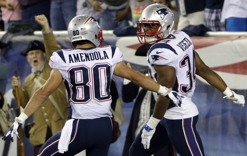 Shane Vereen, right, celebrates with Danny Amendola after catching one of his two touchdown passes Friday night from Tom Brady during the 30-7 victory against Carolina. Vereen, who has had injury woes, is in contention to become the Pats' primary running back.