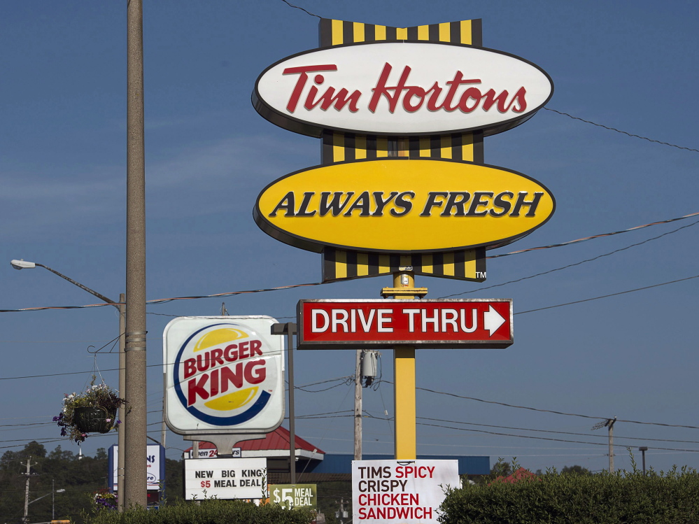 Burger King and Tim Hortons signs stand in Lower Sackville, Nova Scotia. Burger King is in talks to buy Tim Hortons, in hopes of creating a new company headquartered in Canada.