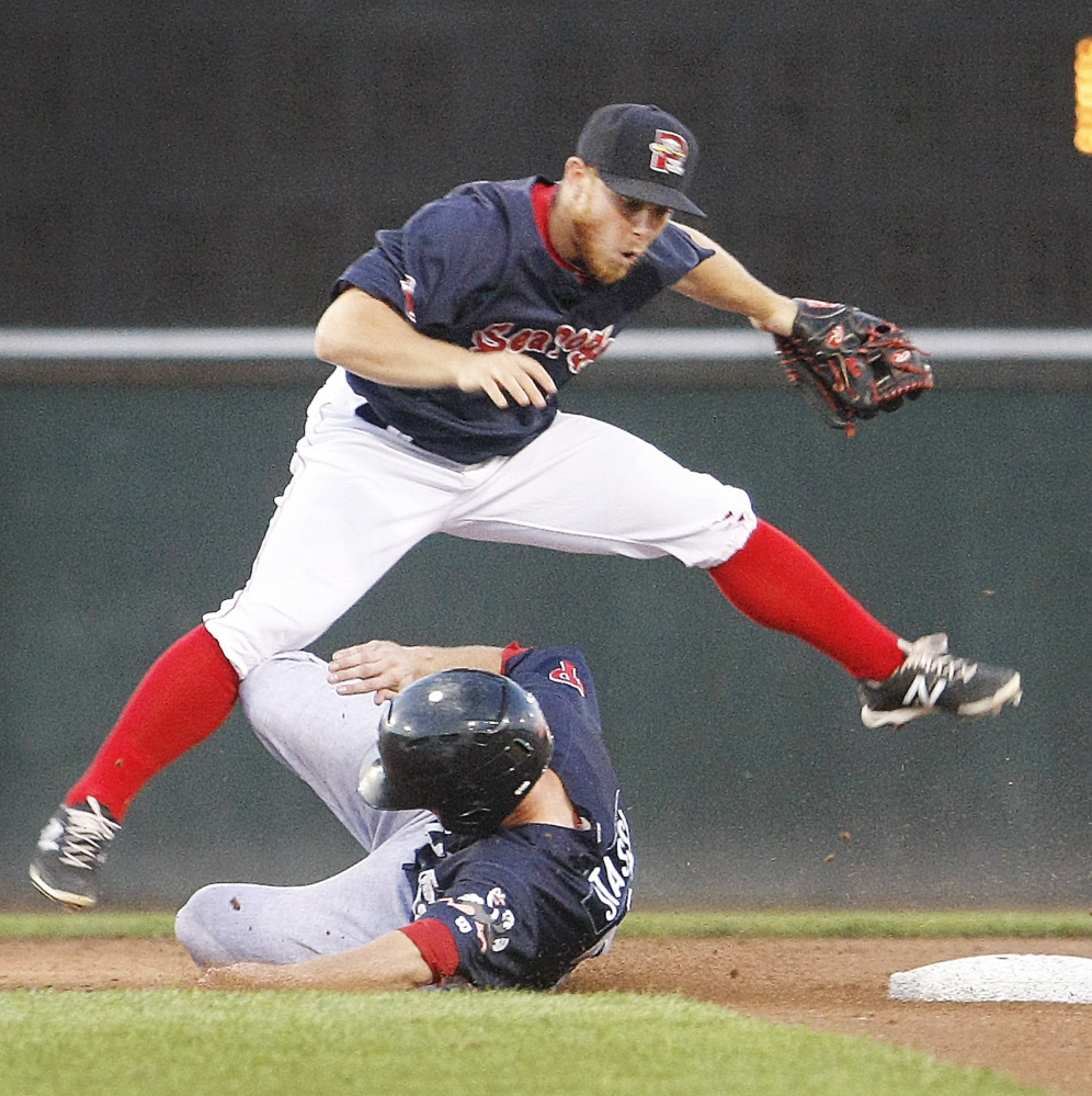 Sean Coyle leaps over Reading's Brock Stassi after making an out at second base and attempting the throw to first base in the second inning Monday night at Hadlock Field.