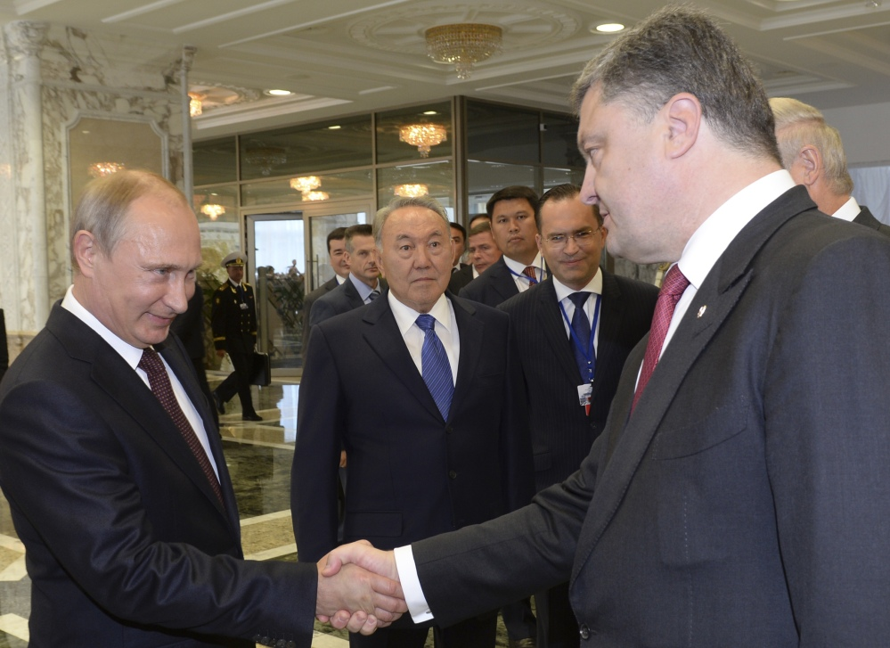 Russian President Vladimir Putin, left, shakes hands with Ukrainian President Petro Poroshenko, right, as Kazakh President Nursultan Nazarbayev looks on, in Minsk, Belarus, on Tuesday.