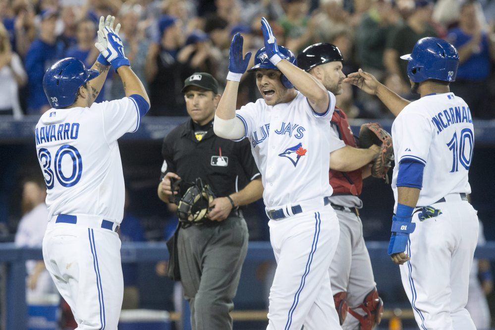 Toronto Blue Jays' Danny Valencia, center, celebrates with Dioner Navarro, left, and Edwin Encarnacion after hitting a three run homer off Boston Red Sox pitcher Junichi Tazawa during seventh inning American League baseball action in Toronto on Wednesday, Aug. 27, 2014. (AP Photo/The Canadian Press, Chris Young)