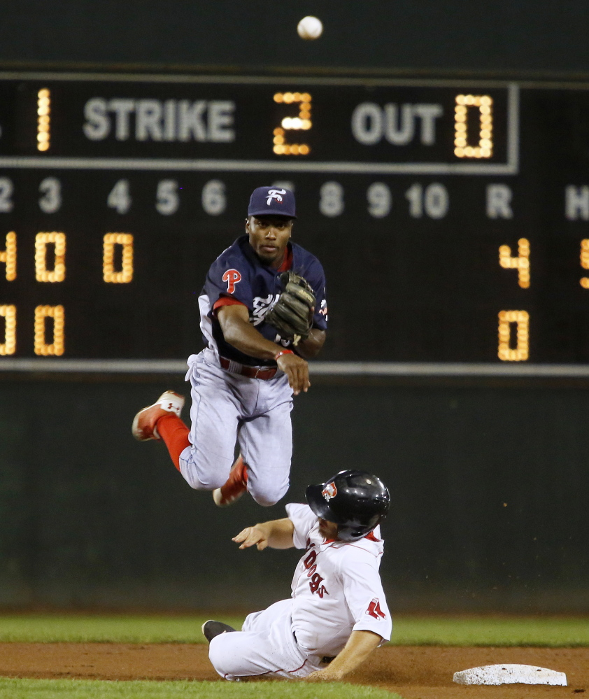 Albert Cartwright of Reading leaps away from the sliding Sean Coyle of the Portland Sea Dogs and throws to first to complete a double play Wednesday night during Reading's 5-2 victory at Hadlock Field.