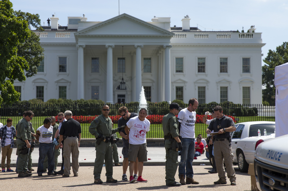 Protesters rally outside the White House over immigration reform Thursday. Reluctant to be seen as stalling for political reasons, the administration suggested that if the decision slips past summer, it would be because of the situation on the border, not the election.