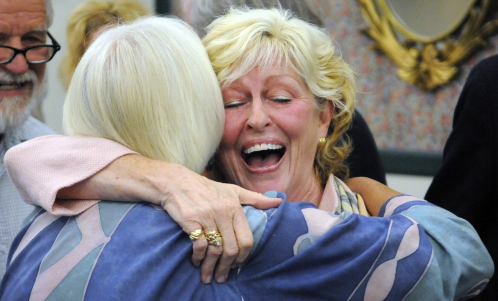 Gilda Nardone, executive director of Women, Work and Community, left, hugs University of Maine at Augusta President  Allyson Handley after the announcement of the plan to give the Gannett Building on Water Street in Augusta a new name — Handley Hall. Nardone's group has offices on top floor of the downtown building.