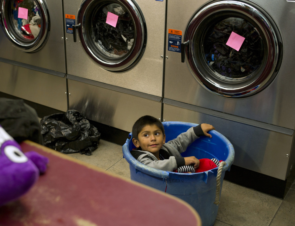 Jose Cortez, 4, sits in a laundry basket while waiting for his mother to finish their laundry.