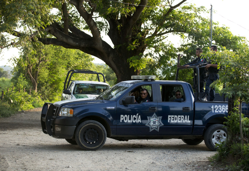 "Federal police and immigration vehicles patrol near the railroad tracks as a northbound freight train departs from Arriaga, Mexico. A crackdown seems to be keeping women and children off the train, known as ""The Beast."""