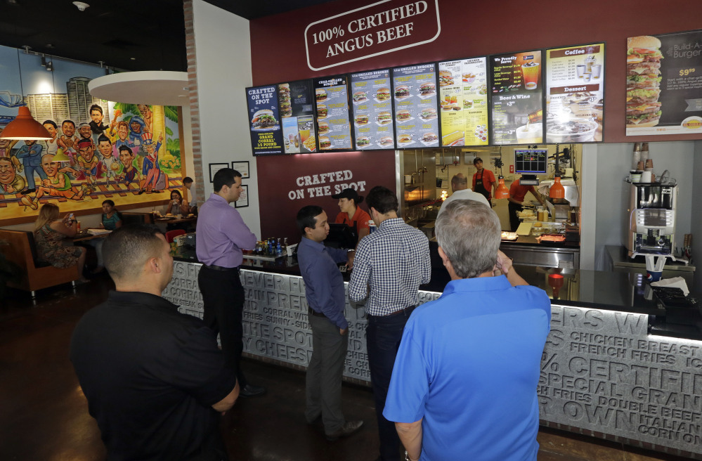 Customers line up to order lunch at El Corral restaurant in Miami. Colombian hamburger chain El Corral has over 200 locations in Latin America and  arrived to the U.S. in early 2013.