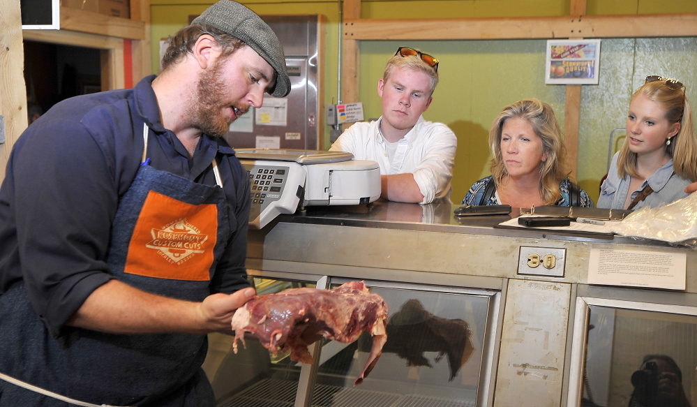Evan Mills, left, butcher for the Rosemont meat department, explains the different cuts of meat he is cutting from a sirloin carcass to the Peddle family of Portland. Joanie Peddle, second from right, ordered four one-pound strip steaks from him as children Conor Peddle, left, and Shannon Peddle, right, look on.