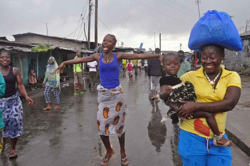 A woman celebrates Saturday as she and others react in a West Point street in Monrovia, Liberia, after learning a section of the city that had been quarantined will be reopened.