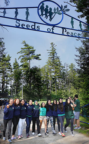 Campers join arms and sing songs as they make their way to opening ceremonies at Seeds of Peace. Derek Davis/Staff Photographer