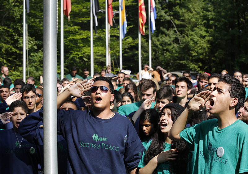 """Abed-Al-Raheem, center, leads fellow Palestinian campers in singing the national anthem """"Fida'i"""" as the Palestinian flag is raised during opening ceremonies at Seeds of Peace. Derek Davis/Staff Photographer"""