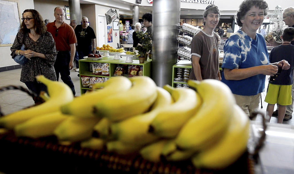 Market customers react to Jonathan Niederer as he sells bananas. Shawn Patrick Ouellette/Staff Photographer