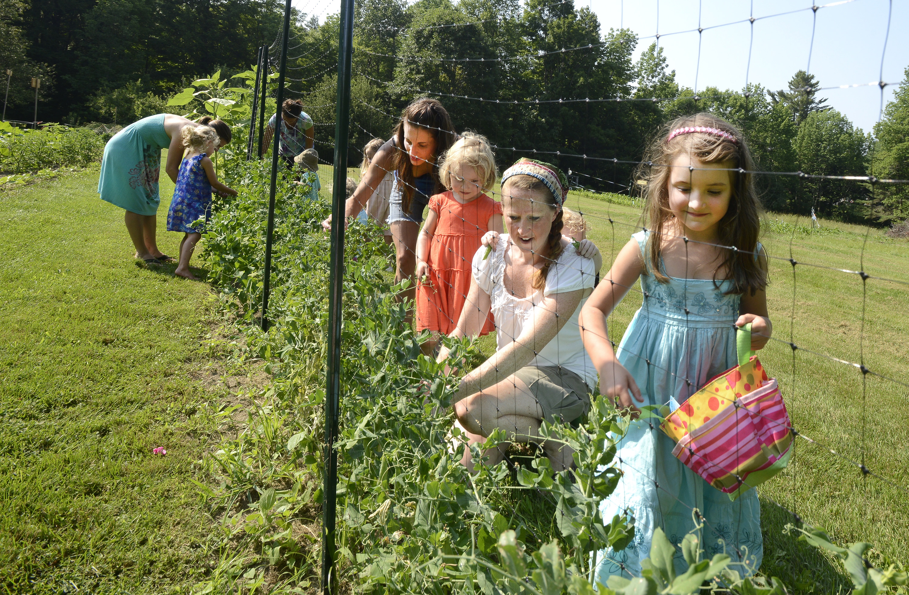 Stephanie O'Neil (in the white shirt) conducts a gardening class for mothers and their children at her farm in West Pownal