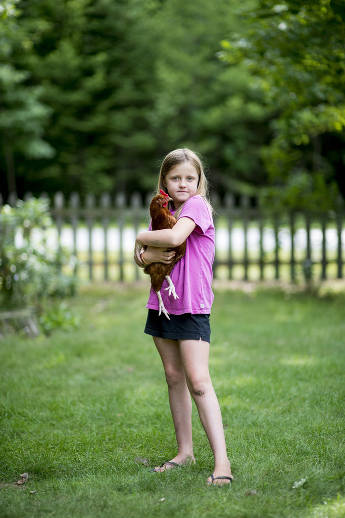 Maezy Gleason hugs her chicken at her family's home in Standish.