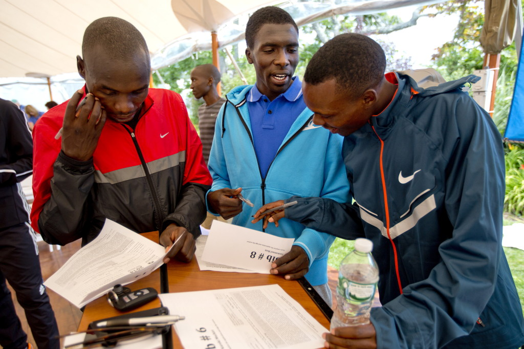 Three of the Beach to Beacon's expected front runners, from left, Stephen Kosgei Kibet, Emmanuel Bett and Bedan Karoki – all of Kenya – fill out the paperwork and get their bibs Friday for Saturday's big race. Gabe Souza/Staff Photographer