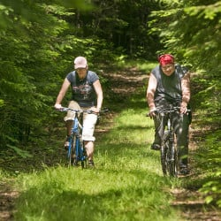 Reinelle Robinson, left, and her son Cordell Guptill of Mount Chase bike on a trail along the East Branch of the Penobscot River. Biking is one of the recreational activities being promoted by the Katahdin Woods & Water Recreation Area.