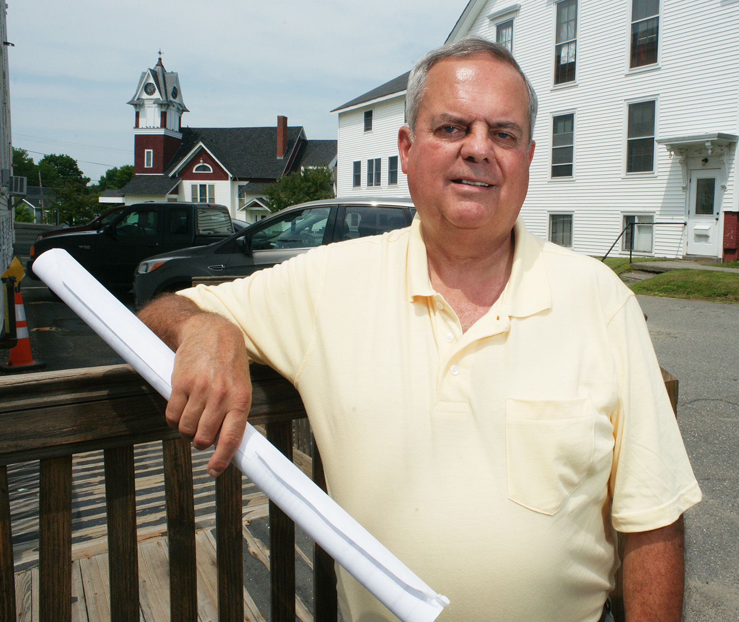 Milo Town Manager David Maynard, holding a property map of the town's business park as he leans on the porch of Milo Town Hall, says that a proposal to dredge Searsport harbor would bring good-paying jobs to Milo and other towns in Maine's economically depressed interior. A developer has proposed building a wood products plant in the business park, but only if the dredge project moves forward. Milo is linked to Searsport by rail.
