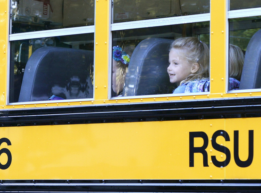 First grade student Elizabeth Baker is all smiles as she joins other RSU 14 students in Windham on the bus for the first day of school. John Patriquin/Staff Photographer