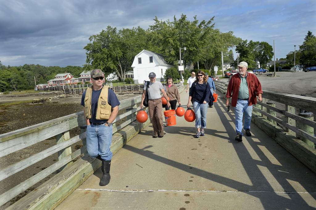 Local lobsterman and members of the Army Corps of Engineers walk out on the Searsport Public Landing as they prepare to go out on Searsport Harbor and Penobscot Bay to discuss a possible dredging project.