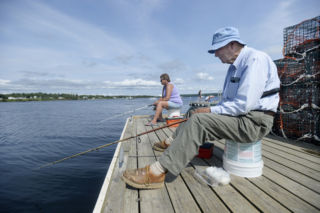 Robert Clark of Searsport , right, and Kriste Wood also of Searsport, fish from the Searsport Public Landing.