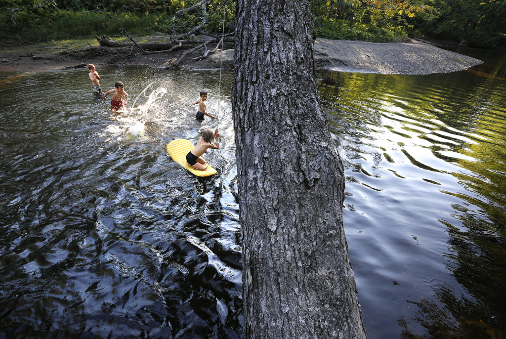 Nathan Kallin, 9, right,  and Madeline Kallin, 8, sitting, play with  friends in a stream where they were camping with their family near the Appalachian Trail.