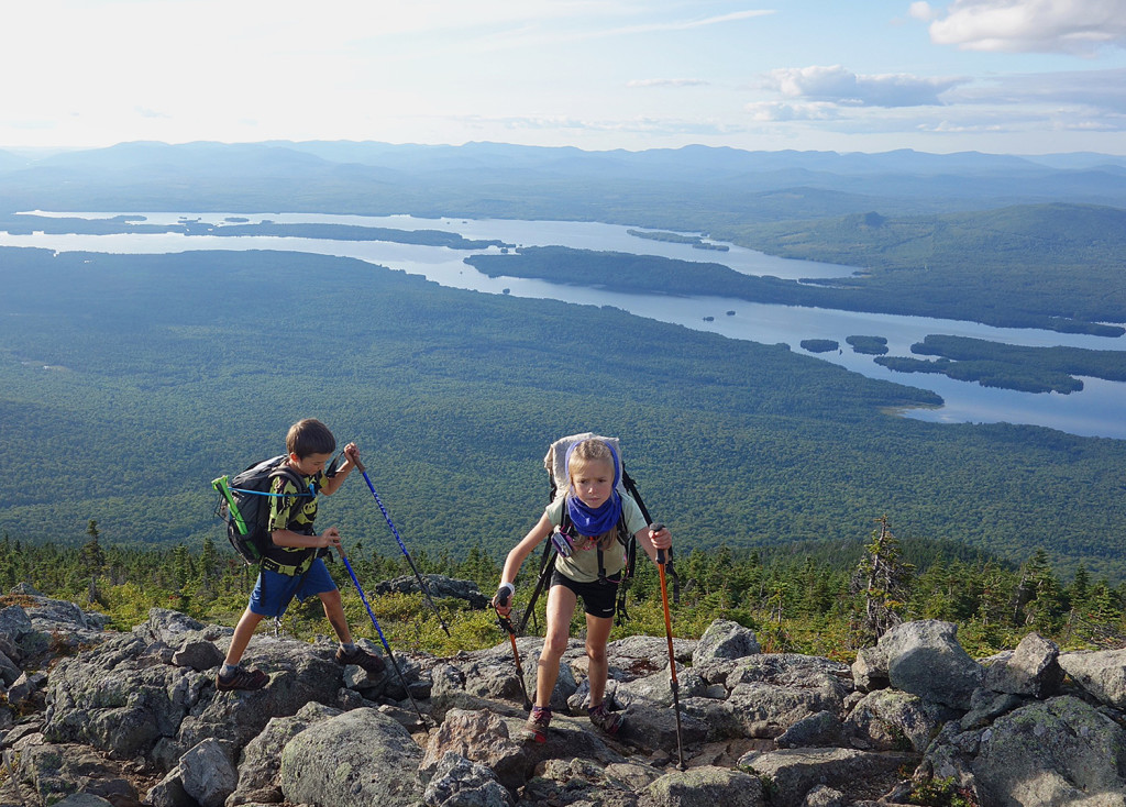 Madeline and Nathan Kallin hike at Bigelow Preserve with Flagstaff Lake in the background.