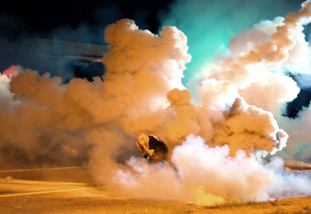 A protester takes shelter from smoke billowing around him Wednesday in Ferguson, Mo. Protests in the St. Louis suburb rocked by racial unrest since a white police officer shot an unarmed black teenager to death turned violent Wednesday night, with some people lobbing Molotov cocktails and other objects at police who responded with smoke bombs and tear gas to disperse the crowd.