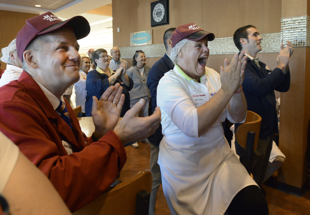 Lisa Lemieux, center right, from Salem, New Hampshire, gets emotional as workers watch their new owner, Arthur T. Demoulas, during a news conference on a TV at the Market Basket in Biddeford.