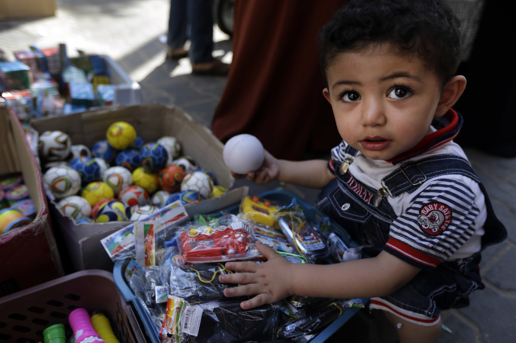 A Palestinian child goes through toys at a vendor's stall in a market in Gaza City, northern Gaza Strip, on Wednesday as a cease-fire between Israel and Hamas that ended a month of fighting held for a second day. The Associated Press