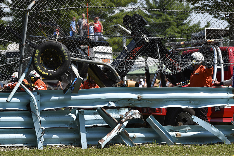 Wreckage from the race car of Michael McDowell (95) protrudes through the catch fence during a NASCAR Sprint Cup Series auto race at Watkins Glen International, Sunday. The Associated Press