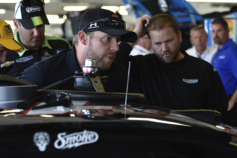 Regan Smith, center, climbs into the race car of Tony Stewart before a NASCAR Sprint Cup Series auto race at Watkins Glen International, Sunday, in Watkins Glen N.Y. Stewart struck and killed a sprint car driver who had climbed from his car and was on the track trying to confront Stewart during a race in upstate New York on Saturday night. The Associated Press