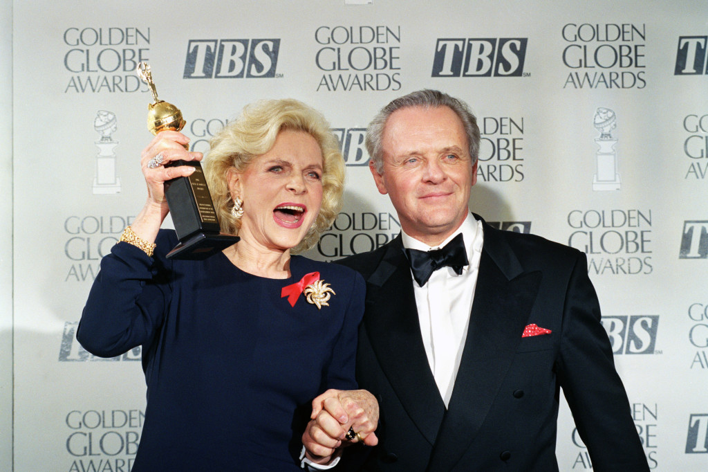 Lauren Bacall holds up her Cecil B. DeMille Award for Lifetime Achievement in January 1993 as she holds hands with actor Anthony Hopkins backstage at the 50th annual Golden Globe Awards in Beverly Hills.