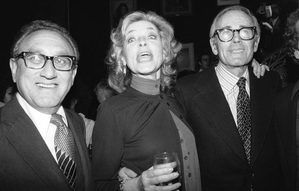 """Lauren Bacall poses with Henry Kissinger, left, and actor Henry Fonda at a party in June 1979 to launch her autobiography,""""By Myself,"""" at the Palace Theater in New York."""