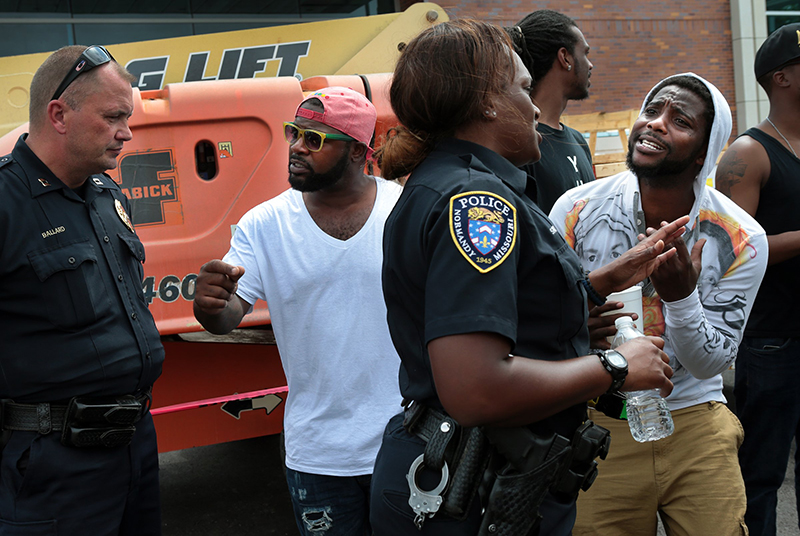 Jamahl Spence, right, pleads his case with a Normandy police officer in front of the Ferguson, Mo. police station on Sunday. The Associated Press.