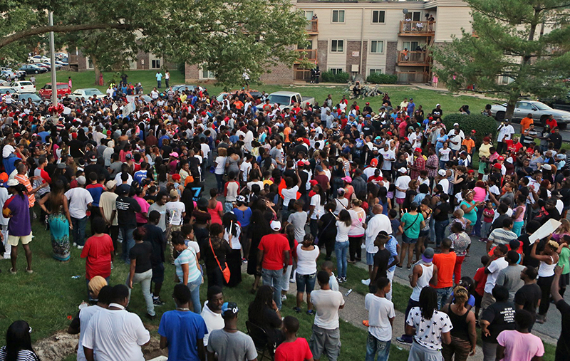 A large crowd gathers at the candlelight vigil, Sunday evening, in Ferguson, Mo. A few thousand people have crammed the street where a black man was shot multiple times by a suburban St. Louis police officer. The Associated Press