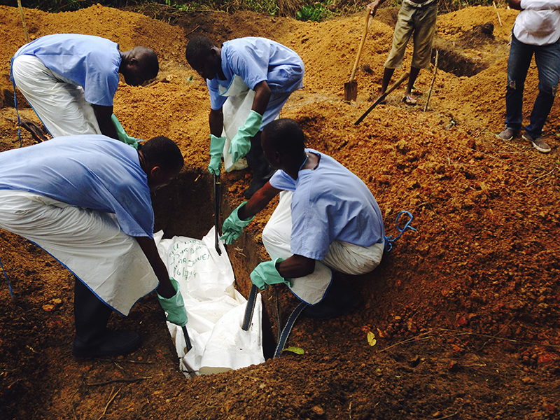 Volunteers lower a corpse, which is prepared with safe burial practices to ensure it does not pose a health risk to others and stop the chain of person-to-person transmission of Ebola, into a grave in Kailahun August 2. Reuters