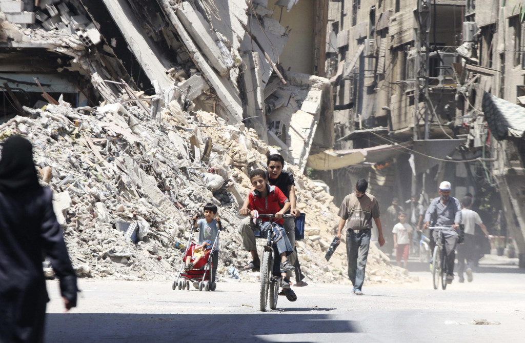 Boys ride a bicycle past other civilians near damaged buildings in the Damascus suburb of Harasta, Syria, on Sunday.