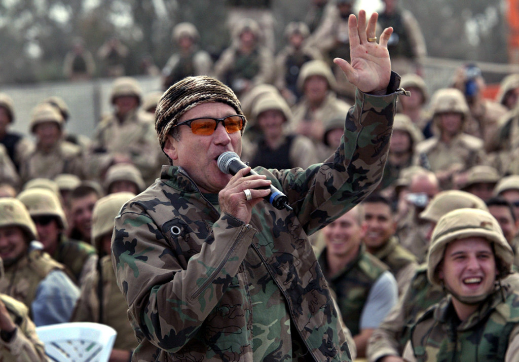 Williams, wearing a camouflage jacket, entertains a cheering crowd of US Army troops at Baghdad airport in 2003.
