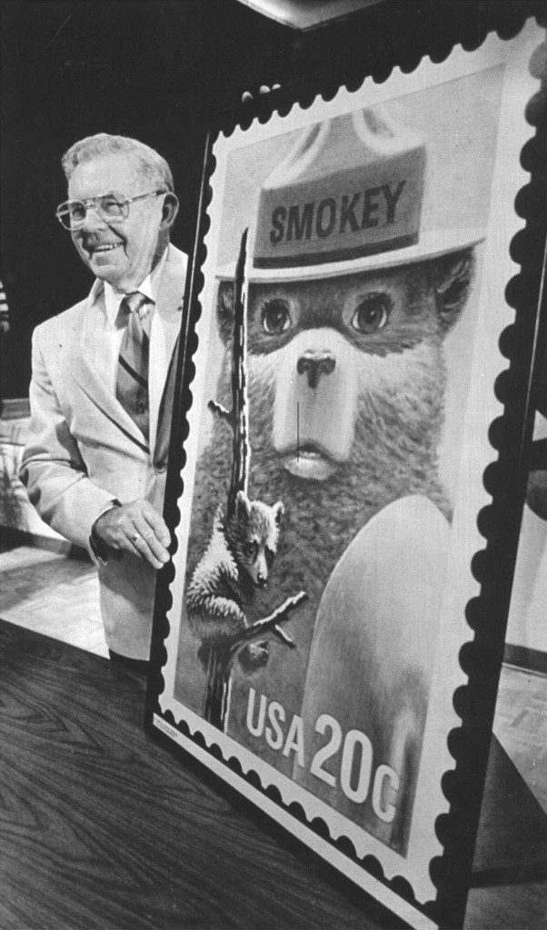 Ray Bell, the man who cared for Smokey Bear after the young cub was rescued from a forest fire 50 years ago, is shown with an oversized copy of the Smokey Bear stamp.