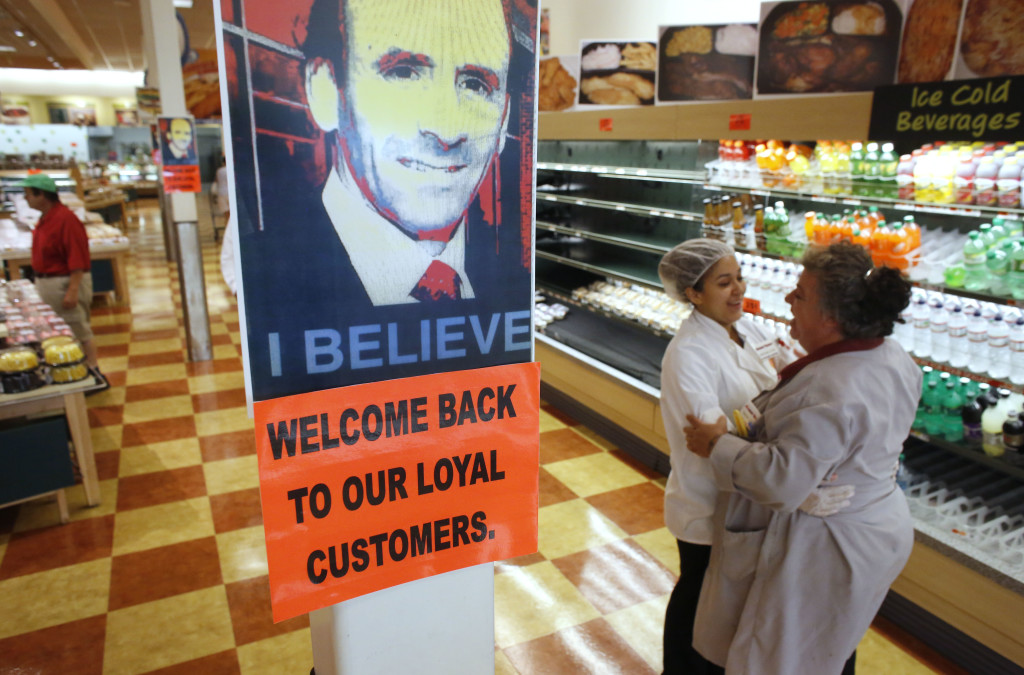 Market Basket employees Cristhian Romero of Chelsea, Mass., left, and Tracie Parker of Lynn, Mass.,  embrace near a likeness of Arthur T. Demoulas at a Market Basket supermarket Thursday in Chelsea.