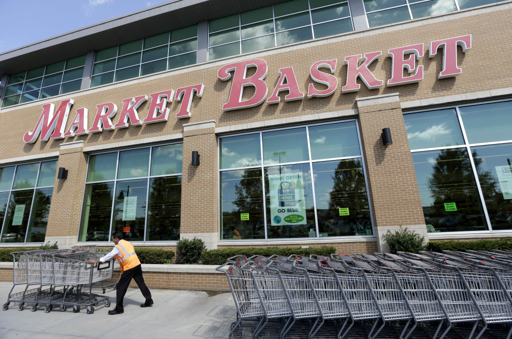 A worker pushes grocery carts in front of a Market Basket supermarket Thursday in Chelsea, Mass.