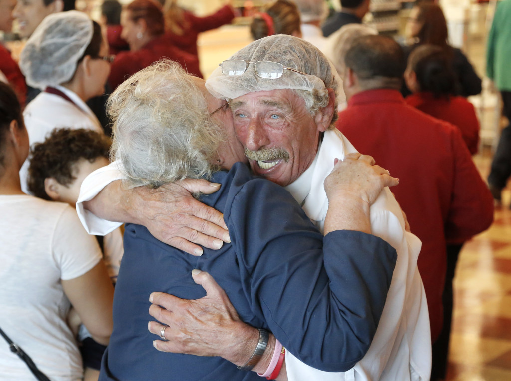 Market Basket meat manager Bob Dietz of Methuen, Mass., hugs cashier Mary Olson of Chelsea, Mass., after watching a televised speech by restored Market Basket chief Arthur T. Demoulas at a store Thursday in Chelsea, Mass.