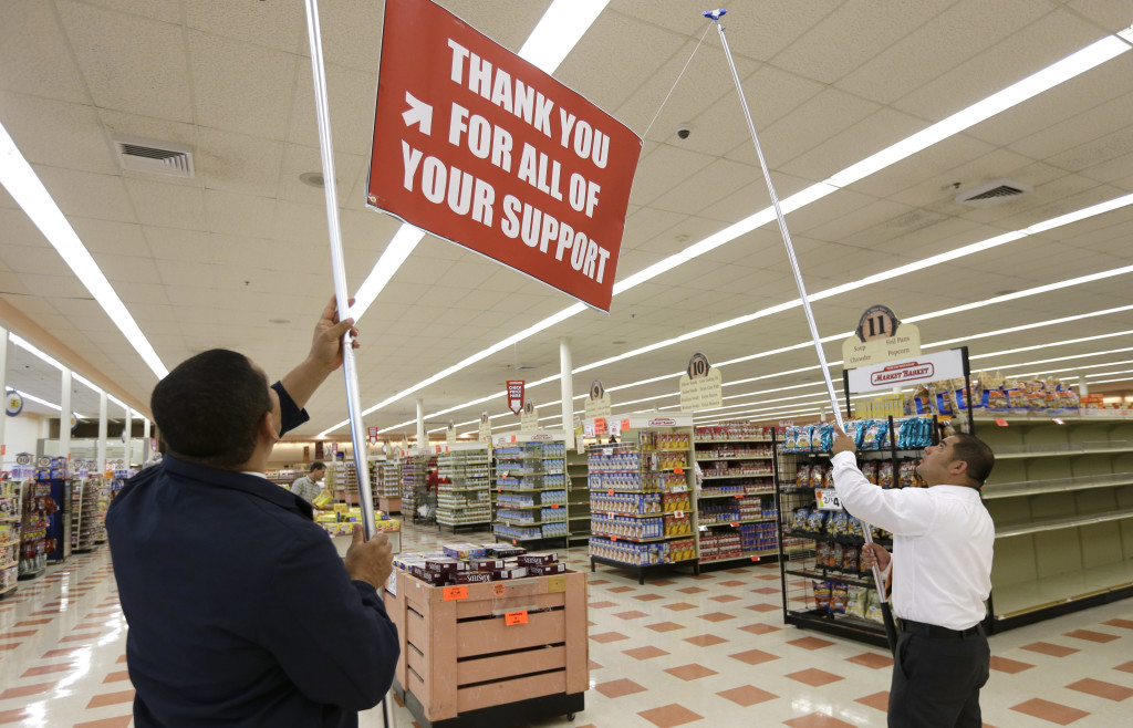 Market Basket employees Eduin Uribe, left, and Kevin Pineda hoist a sign at a Market Basket supermarket Thursday in Chelsea, Mass.