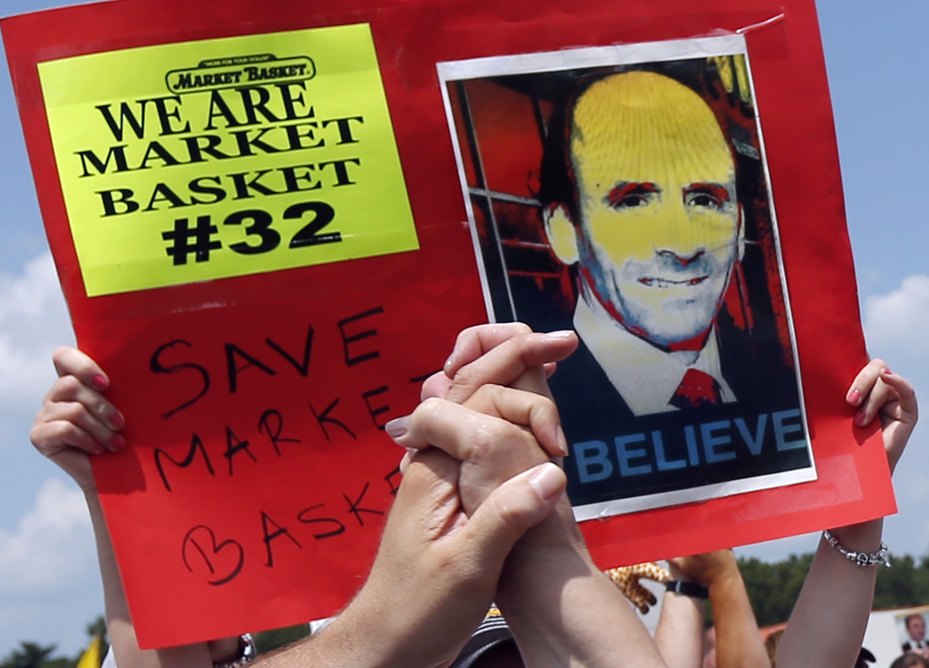Protesters clasp hands at a rally outside Market Basket in Tewksbury, Mass., Aug. 5, in support of the company's ousted CEO.