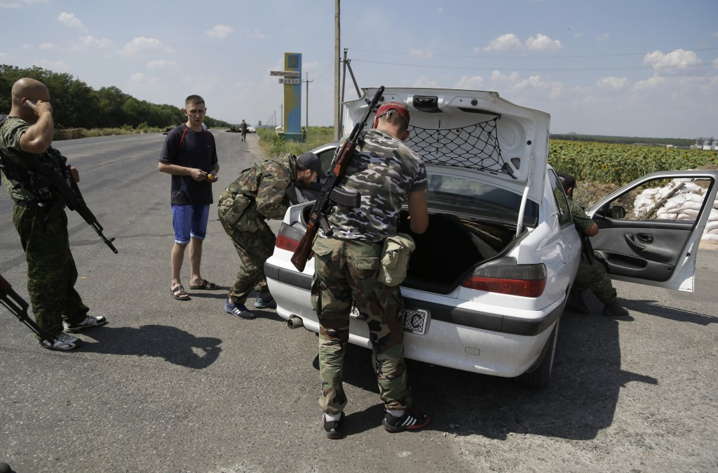 Pro-Russian rebels search the car of a local resident at a checkpoint near the city of Donetsk, eastern Ukraine, Wednesday. Air strikes and artillery fire between pro-Russian separatists and Ukrainian troops in Donetsk have brought the violence closer than ever to the city center, as Kiev's forces move in on the rebel stronghold. The Associated Press