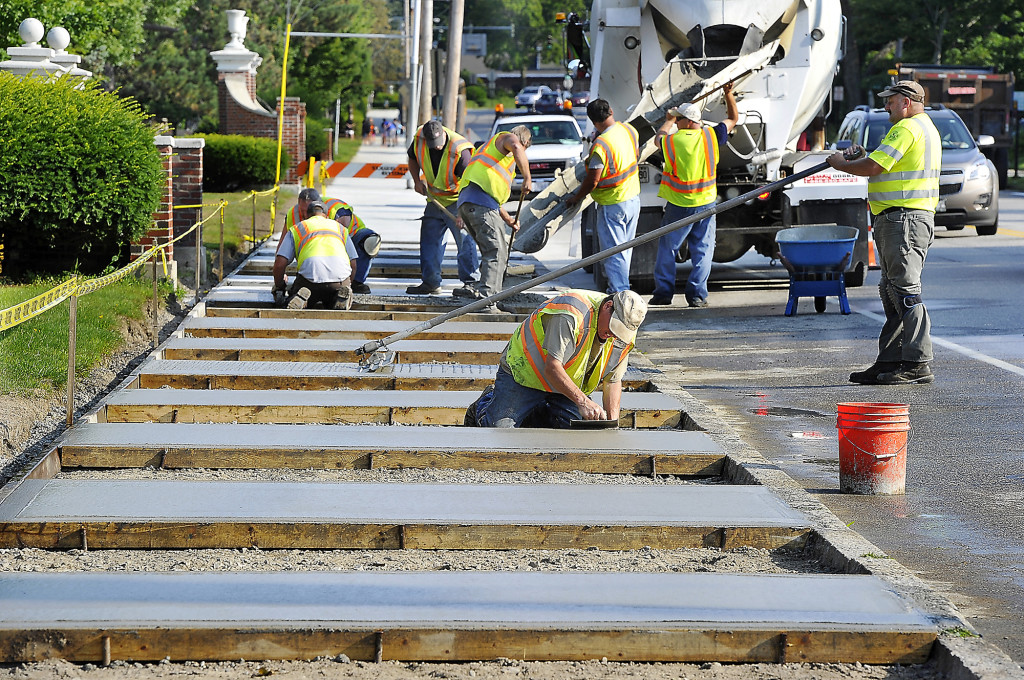 Scott Merritt, left, edges the fresh concrete as Dave Shaw settles each sectioned pour. They and the rest of the Construction Division of Portland Public Services put a new concrete sidewalk in front of Deering High School on Monday. Gordon Chibroski / Staff Photographer