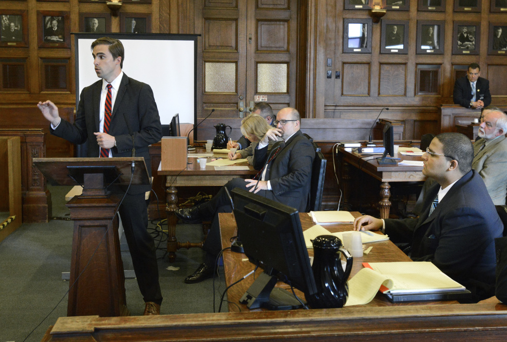 Defense attorney Dylan Boyd presents his opening statement to the jury in the murder trial of Anthony Pratt Jr., seated at lower right, at the Cumberland County Court house in Portland on Monday. Assistant Attorney General Donald Macomber listens in background.