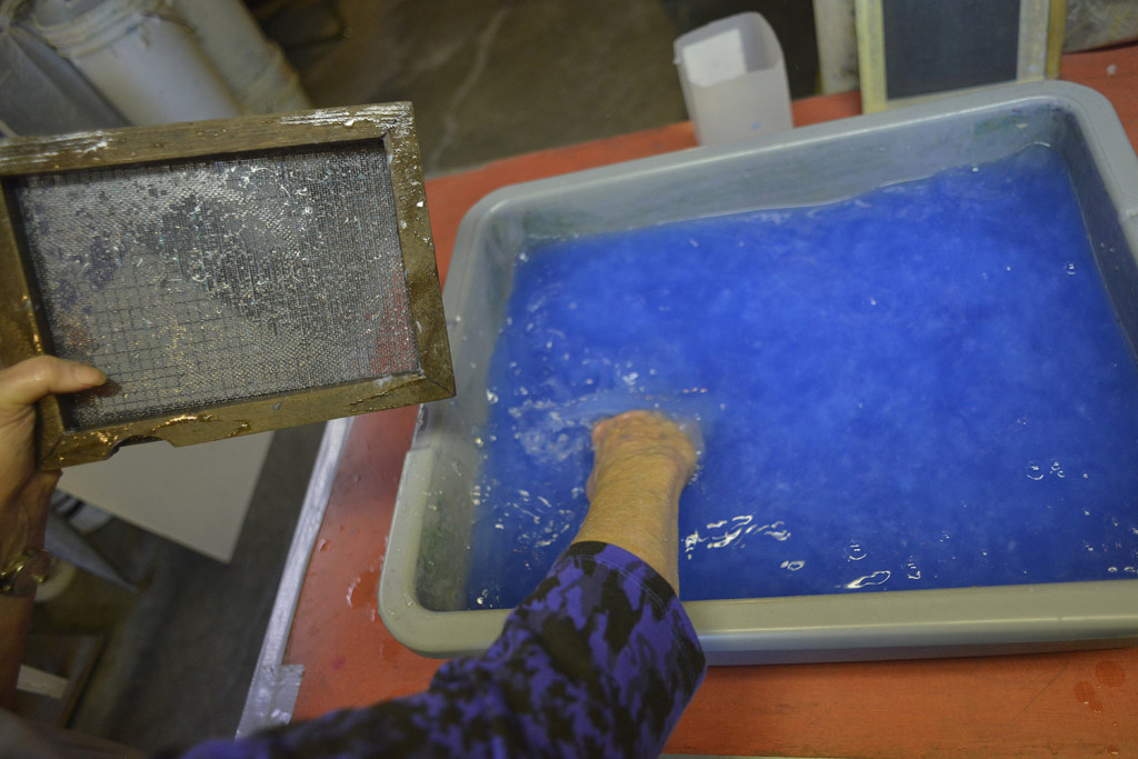 Kuhl uses a wove mould and a deckle as she stirs pulp.